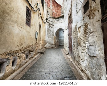 A narrow street in the old city of the Fez medina in Morocco leads up the hillside through an arch.