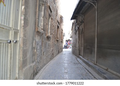 Narrow street in Sanliurfa city center from Anatolia, Turkey with metal shutter and beige door, stone wall and window
