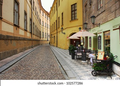 Narrow street with small hotel and outdoor restaurant in historic part of Prague, Czech Republic.
