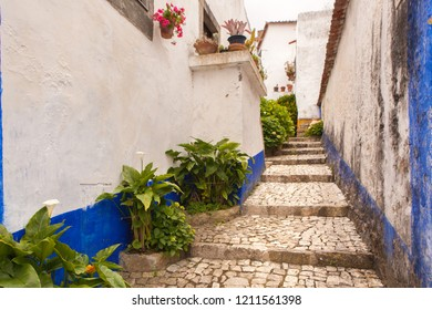 Narrow street with steps between colorful houses in medieval town of Obidos, Portugal. In the Medieval Portuguese City of Obidos.