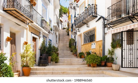 Narrow street with steps, white houses and potted plants in ancient neighborhood El Barrio or Casco Antiguo Santa Cruz in Alicante old town on hillside. Costa Blanca on Mediterranean sea coast, Spain