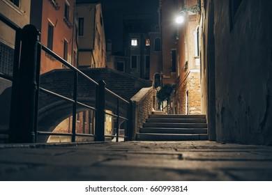 Narrow street and stone bridge at night in Venice, Italy