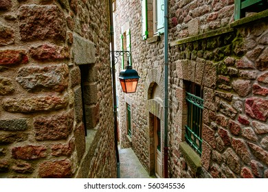 Narrow street with stone houses and vintage lamp in Mont Saint Michel village center, in Normandy , France