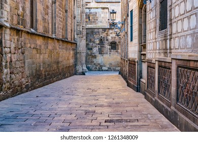 Narrow street surrounded by medieval buildings at gothic district in barcelona city, spain