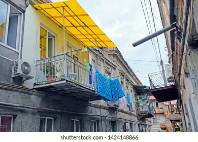 Narrow street in Tbilisi with old architecture. Hanged blankets on the ropes on the balcony. People dry clothes and laundry on the balcony.