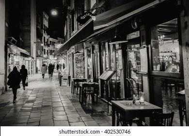 Narrow street in Venezia at night. Black and white photo.