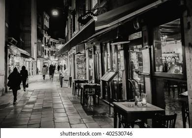 Narrow street in Venezia at night. Black and white photo.