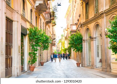 Narrow street with walking people and trees in ceramic pots in Milan, Italy