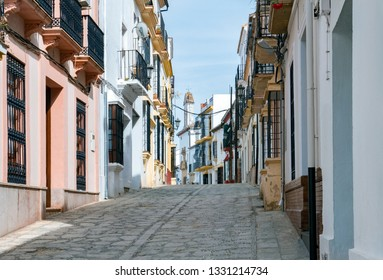 Narrow street with white facades of houses in historic district of Ronda, Spain