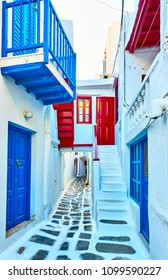 Narrow street with white houses in Mykonos town, Greece