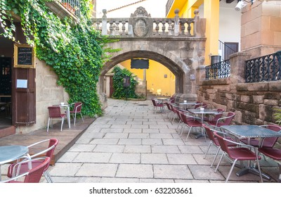 Narrow streets & charming alleys featuring dining al fresco, as an empty outdoor cafe awaits customers.  Barceloneta is Barcelona City's 18th century built neighbourhood