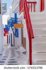The narrow streets of the island with blue balconies and stairs