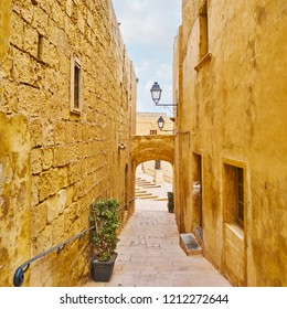 The narrow streets of Rabat Citadel, lined with tall stone walls of preserved edifices, Victoria, Gozo, Malta.