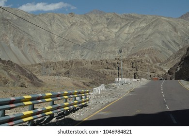 Narrow, twisting road along the Indus River in deep valley, Ladakh, India