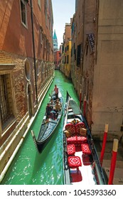 Narrow Venetian canal with gondolier and tourists in the gondola.