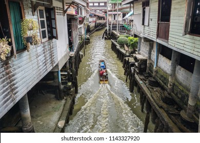 Narrow water canal with boat and traditional thai house, authentic and  genuine Thailand