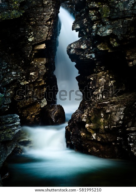 Narrow waterfall in a crevice. Rondane mountains, Norway