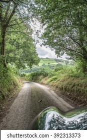 A narrow Welsh forest road with view of green pastures ahead, reflected on the bonnet of a green British car.