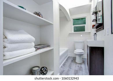 Narrow white bathroom interior with open shelves and gray hardwood floor.