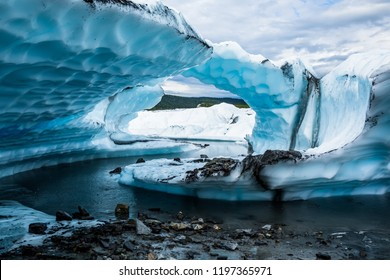 A narrow, winding river of meltwater on the Matanuska Glacier carved several large fins of overhanging ice. The layers of fins Appear to form an arch from the side.