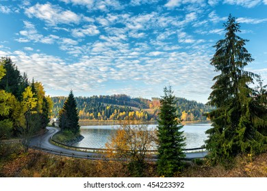 Narrow winding road along the lake, autumn landscape with deep blue cloudy sky, National park Slovak paradise, Slovakia - Shutterstock ID 454223392