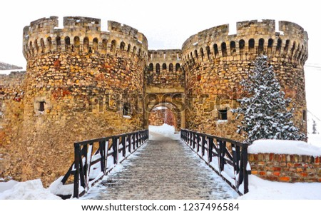 Narrow wooden bridge and medieval towers with stone bricks wall gate in Belgrade fortress castle Kalemegdan under snow in winter time, Serbia