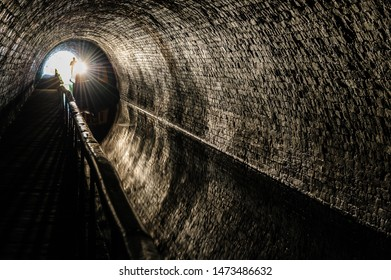 Narrowboat with headlight travelling through the Chirk Tunnel on the Llangollen canal