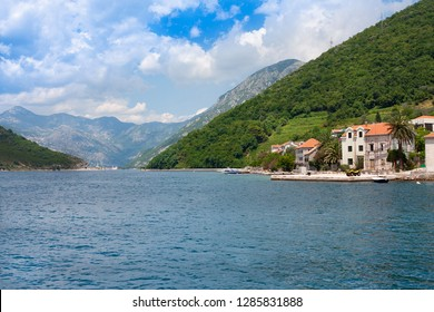 Narrowest part of the Bay of Kotor, Verige Straits. Church and houses with red title roofes. Kamenari. Montenegro