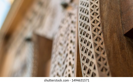 Narrow-focus detail of a carved wooden door handle at the entrance to a restored traditional arabian house.