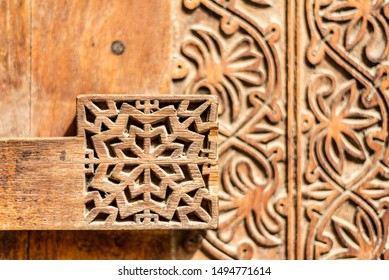 Narrow-focus detail of a carved wooden door lock at the entrance to a restored traditional arabian house.