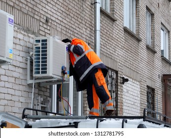 Narva, Estonia 2019-02-14. Street of Narva. Worker iworker installing air conditioner  on the wall of the building.