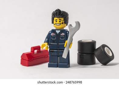 NARVA, ESTONIA - JANUARY 31: A lego toy of a mechanic reparing a car with tires and instruments in Narva, Estonia on January 31, 2015