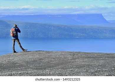 Narvik, Norway, 2019: Photographer taking photo on the hill in Narvik, northerly of the Arctic Circle, mountains, forrests and valleys in the background, beautiful sunny day