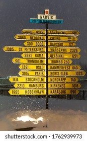 Narvik, Norway - December 4, 2019: The famous yellow sign post in the city center lets locals and visitors alike know their distance to other cities and countries, especially the North Pole.