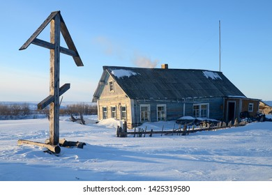 Naryga village, Nenets Autonomous Okrug, Russia - April, 2014: Vow cross and old wooden traditional house, monuments of local history and culture.