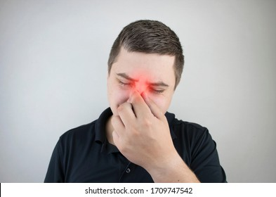 Nasal bridge pain, headache. A man holds his nose with his hand and winces in pain. Signs of acute ethmoiditis