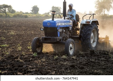 NASHIK, MAHARASHTRA, INDIA 19 NOVEMBER 2017 : Unidentified farmer with tractor preparing land for sowing with cultivator, An Indian farming scene.