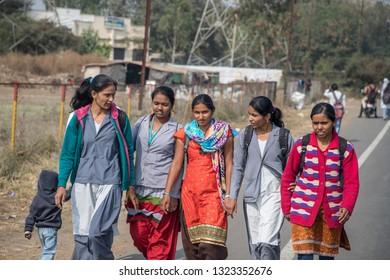 Nashik, Maharashtra, India -January 9, 2018: College students in Sinnar Dist walking and chatting along Nashik-Pune Road after school