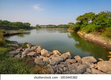 Nashik,17, December, 2019 : View of  man- made rainwater reservoir surrounded by greenery for agriculture against blue sky ,Nashik, Maharashtra ,India, Asia