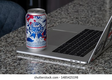 """Nashville, Tennessee - 22 August, 2019: """"Pabst Blue Ribbon"""" beer can on top of a silver laptop on a kitchen island"""