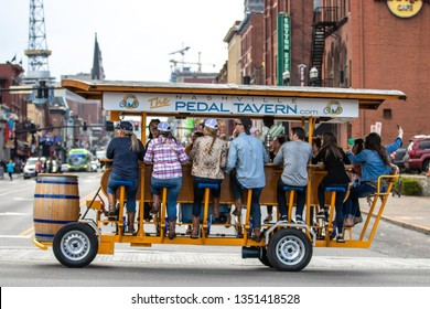 Nashville, Tennessee - March 25, 2019 : A Pedal Tavern party bike on a beautiful sunny day crossing Broadway.