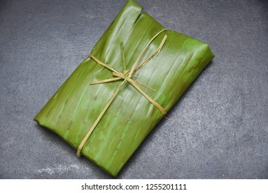 Nasi Bakar or Aromatic rice wrapped In banana leaves,Indonesia. seasoned rice dish with fried chicken or salted fish, mushroom, vegetable, sambal. wrapped in banana leaf and grilled upon charcoal fire