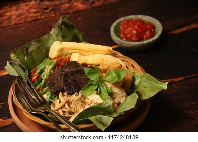 Nasi Bakar. Sundanese dish of char-grilled rice and fermented soybean in banana leaf; topped with beef jerky, green beans, salted anchovies and crackers.