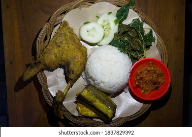 Nasi Bebek Goreng or spiced fried duck served with rice, fresh vegetables and chilli. Lowlights photos.