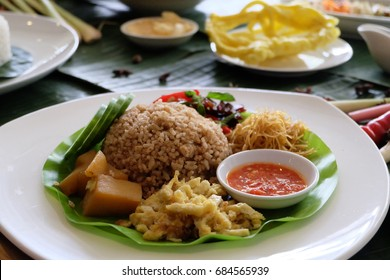 Nasi campur or mixed rice is Indonesian food containing red/brown rice, side dishes, sliced ??omelet and chili sauce on a plate.
