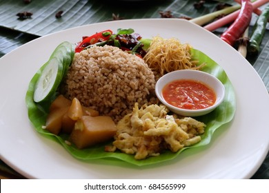 Nasi campur or mixed rice is Indonesian food containing brown/red rice, side dishes, sliced ??omelet and chili sauce on a plate.