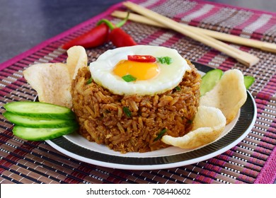 Nasi goreng fried rice with shrimps and egg garnished with fresh cucumber slices and prawn crackers on a plate on a cloth. Asian food.