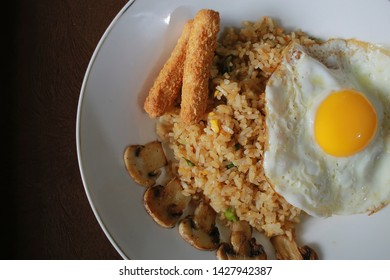 Nasi goreng (fried rice) with sunny side up egg, mushroom, chicken stick nugget. Served on a white plate above the table. Top view close up detail