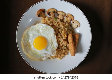 Nasi goreng (fried rice) withsunny side up egg, mushroom, chicken stick nugget. Served on a white plate above the table. Top view close up detail
