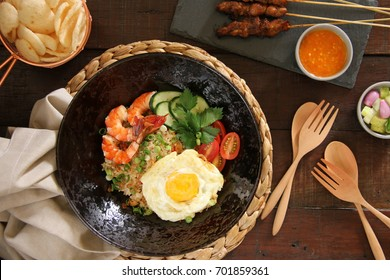 Nasi Goreng Gourmet. Indonesian staple dish of fried rice, served luxuriously with prawns, fried egg, chicken satay, shrimp crackers, cucumber pickles and chili sauce.